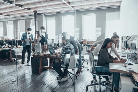 office with multiple people at desks collaborating